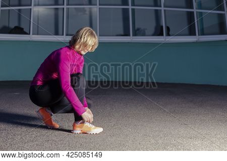 Mature Female Sport Ideas. Active Female Runner Tighten Up Her Shoelaces During Jogging Training Exe