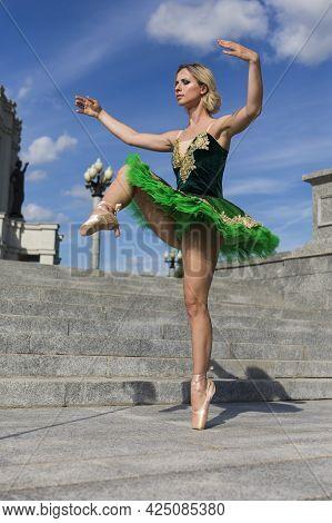 Dancing Concepts. Smiling Professional Caucasian Ballet Dancer In Green Tutu Dress Posing In Dance O