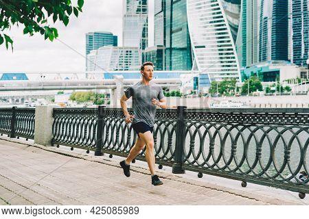 Young Athlete Man Runner Running At Summer Morning, Background Urban City Street. Sports Training. F