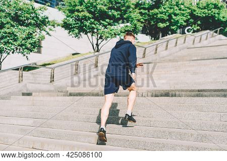 Young Athlete Man Runner Running Up And Down On City Stairs In Summer On Morning Run, Background Urb