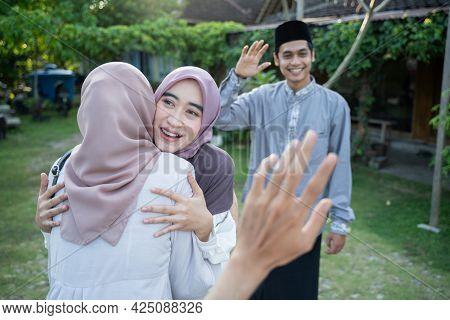 A Woman Wearing A Headscarf Hugs A Female Friend