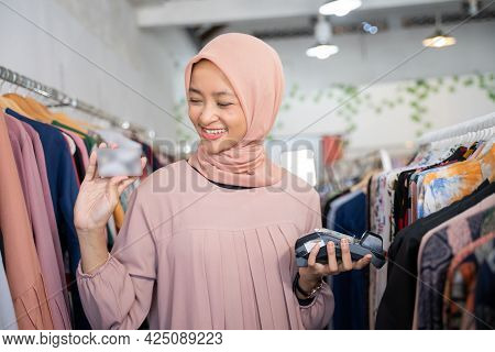 Smiling A Girl In Veil Holding A Credit Card And An Electronic Data Capture Machine