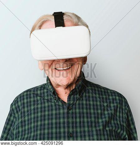 Cheerful senior man wearing  virtual reality goggles mockup