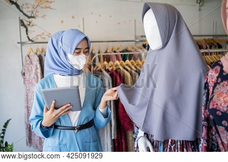 A Veiled Woman Wearing A Mask Uses A Tablet While Holding A Headscarf Mannequin