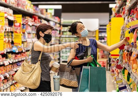 Happy Two Asian Woman Friends Shopping Discounted Products In Supermarket