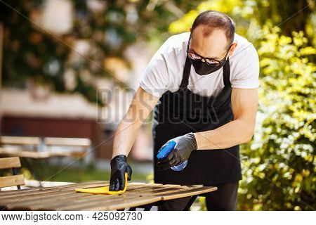 A Waiter In A Protective Mask And Gloves Clean Table With Disinfectant And Wipe Before Welcome Custo