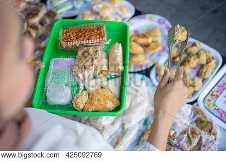 Female Buyer Uses Tong Tongs To Select And Take The Fried Food To The Plastic Tray