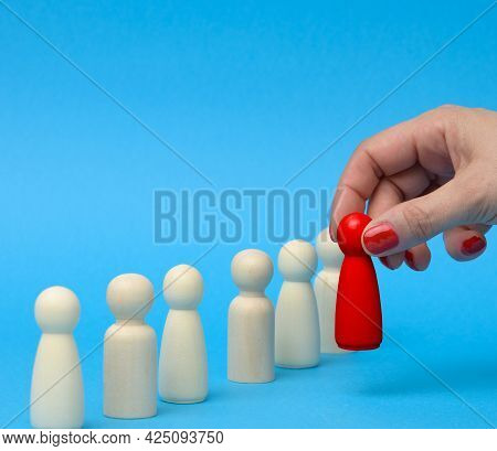 Emale Hand Holds A Wooden Red Figurine Chosen From The Crowd. The Concept Of Finding Talented Employ