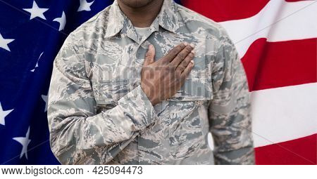 Composition of midsection of male soldier with hand on heart, against american flag. patriotism, independence and celebration concept digitally generated image.