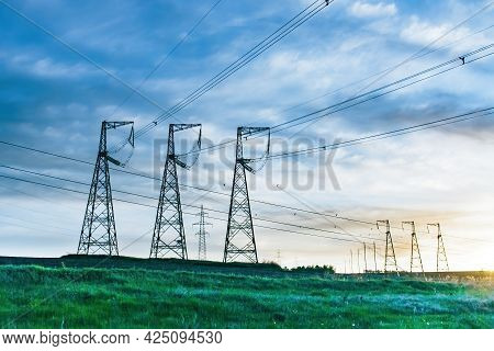 Overhead Power Line Transmission Tower At Sunset. Electricity Pylon And High Voltage Grid Tower With