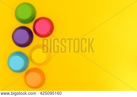 Paper Molds For Making Cupcakes On Yellow Background. Colorful Cupcake Molds.