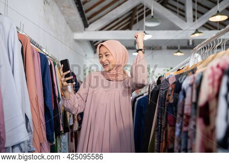 A Beautiful Girl In A Headscarf Felt Excited To Raise Her Hand While Holding A Smartphone