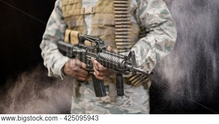 Composition of midsection of male soldier holding gun, against smoke on black. conflict, independence and military concept digitally generated image.