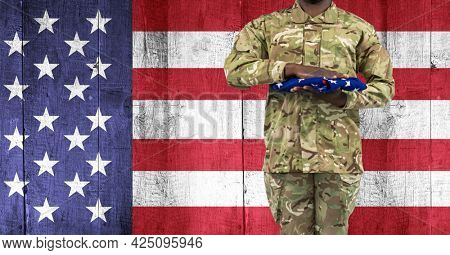 Composition of midsection of soldier with hand on folded american flag, against american flag. patriotism, independence and honour concept digitally generated image.