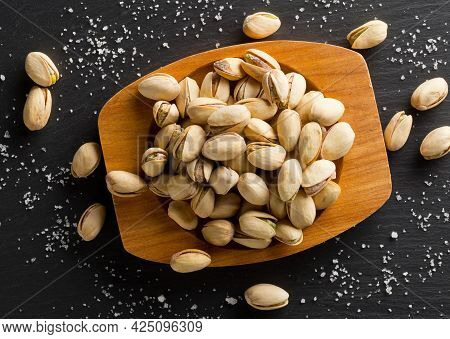Heap Of Salted, Roasted Green Pistachio Nuts Snack In Wooden Bowl On Black Background With Sea Salt,