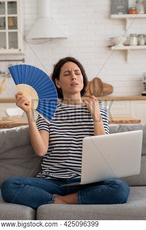 Tired Millennial Woman Suffers From Stuffiness And An Inoperative Air Conditioner, Waving Blue Fan S