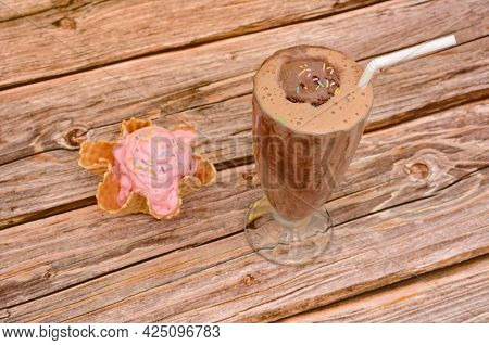 Chocolate Milkshake In A Glass Cup On A Wooden Table.