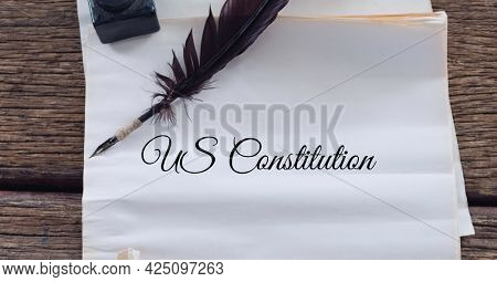 Composition of text us constitution, with quill pen and inkwell on antique documents. patriotism, independence and american constitution celebration concept digitally generated image.