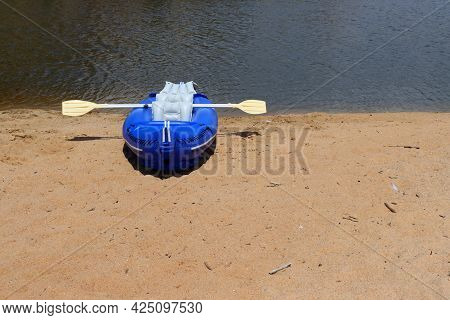Blue Rubber Boat And Oars On The Sandy Bank Of The River. Inflatable Boat