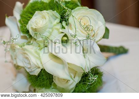 Close View On Calla Flowers With Wedding Rings In Warm Colors. High Quality Photo