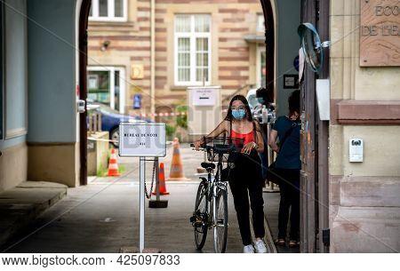Strasbourg, France - Jun 27, 2021: Woman With Bike Exits French Polling Station Sign Bureau De Vote.
