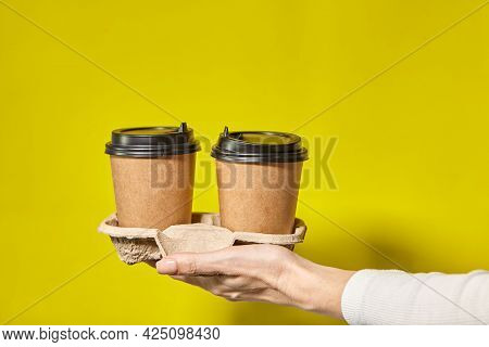 Hands holding two cups brown paper with black lid. Two coffee special offer or promo. Hands holding