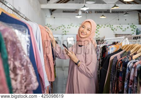 A Beautiful Girl In A Headscarf Smiling At The Camera While Holding A Robe And Smartphone