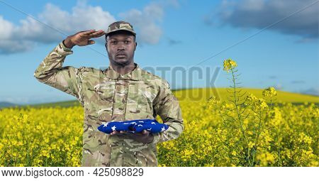 Composition of saluting male soldier with holding folded american flag, on rapeseed field. patriotism, independence and honour concept digitally generated image.