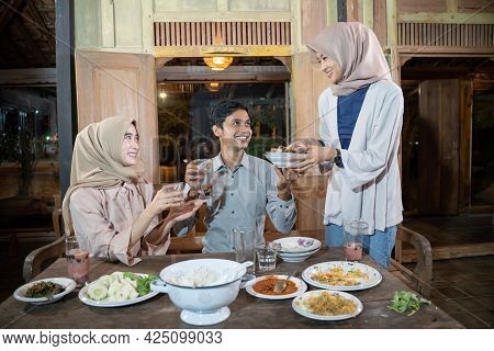 Two Women In Headscarves And An Asian Man Tidying The Dining Table After Iftar Together