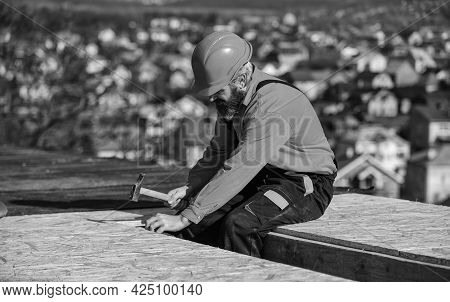Construction Industry And Waterproofing. Roofer Working On Roof Structure Of Building On Constructio