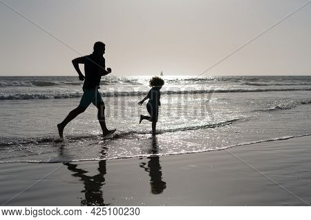 Daddy With Kid Boy Silhouette In Sea Or Ocean. Weekend Family Day. Dad And Child Having Fun