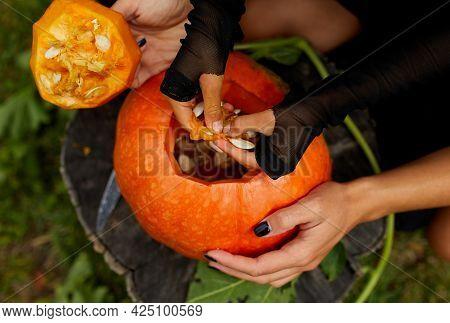 Daughter And Mother Hands Carving Pumpkin For Halloween, Prepares Jack O'lantern