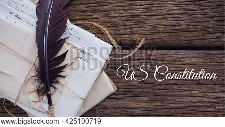 Composition of text us constitution, with quill pen and antique documents on wood. patriotism, independence and american constitution celebration concept digitally generated image.