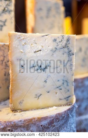 Stacks of whole and cut Stilton cheeses for sale at a market. This is a popular English blue cheese that has had Penicillium roqueforti added to create the characteristic blue veins.