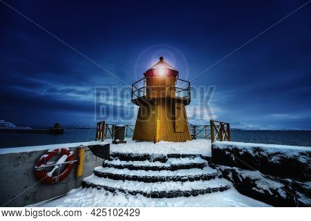 Lighthouse at the entrance to the Old Port, Reykjavik, Iceland. Blue hour shot at dawn during winter, with yellow beacon and snow on the ground.