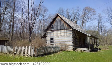 Settler Log Home In The Forest With Garden Surrounded By Picket Fence