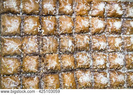 Oriental Sweets Baklava With Nuts In The Form Of Brown Squares Sprinkled With Coconut Shavings. Frui