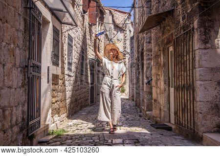 Beautiful Blonde Young Female Traveler Wearing Straw Sun Hat, Taking Selfie While Sightseeing And En