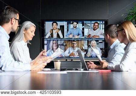 Global Corporation Online Videoconference In Meeting Room With Diverse People Sitting In Modern Offi