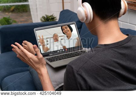 Asian Man Video Conference Meeting With Sick Elderly Father To Encourage And Inquire About Illness.