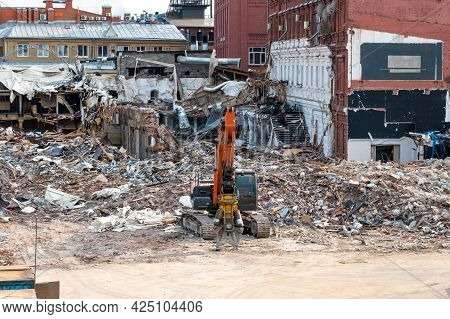 A Crawler Excavator With A Special Manipulator In Front Of A Pile Of Debris From A Destroyed Buildin