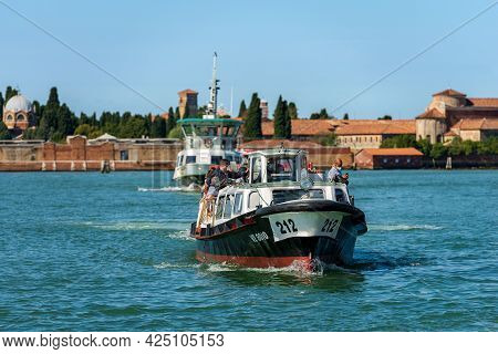 Venice, Italy - June 2, 2021: Ferry Boats Called Vaporetto Crowded With Tourists In Motion In The Ve