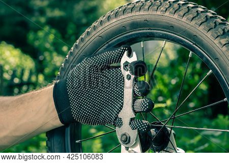 Bicycle Repair. Tightening The Bicycle Wheel. Bicycle Key In A Mans Hand. The Master Maintains The B