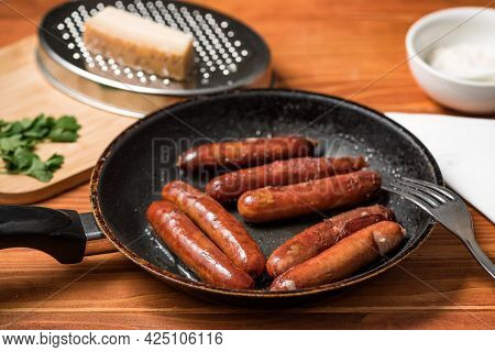 Tasty Fried Sausages In Frying Pan With Parmigiano And Parsley, Over Wooden Background