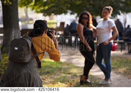 Woman Photographer With Camera In The Park, Photographs People. Professional Photographer, Blogger,