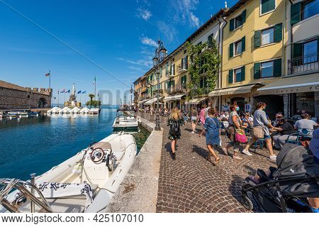 Lazise, Italy - May 26, 2021: Small Port Of The Lazise Village With Moored Boats. Tourist Resort On