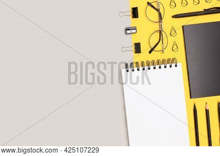Layout Of Black Office Stationery On A Gray And Yellow Background. Neat Workspace With Place For Tex