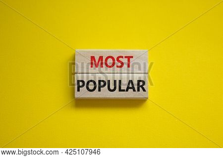 Most Popular Symbol. Concept Words Most Popular On Wooden Blocks On A Beautiful Yellow Background. C