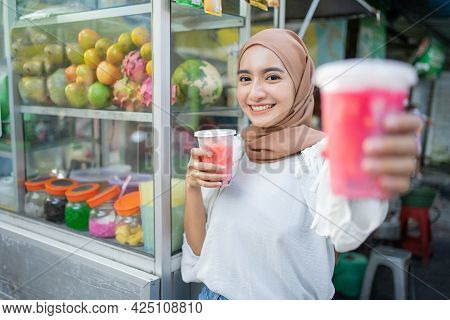 Beautiful Girl In Hijab Smiles At The Camera Holding A Plastic Cup Of Fruit Juice While Standing