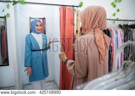 A Woman In A Veil Tries On Clothes In A Changing Room In Front Of The Mirror And Is Shown To Her Fri